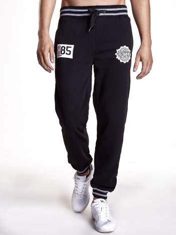 Czarne dresowe spodnie z naszywkami i kieszeniami