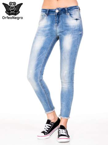 Jasnoniebieskie spodnie jeansowe rurki z poszarpaną nogawką na dole