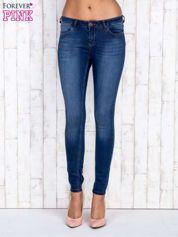 Granatowe jeansowe spodnie rurki z przetarciami