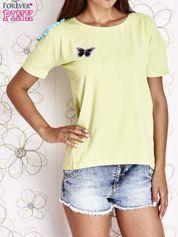 Limonkowy t-shirt z naszywką motyla i pomponami