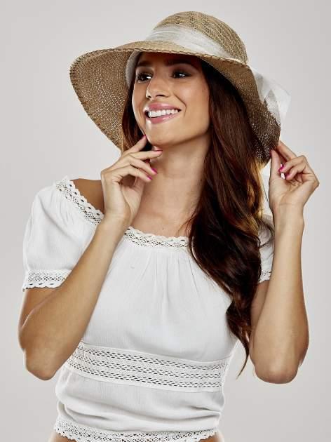 Beżowy kapelusz słomiany z dużym rondem i ozdobną kokardą
