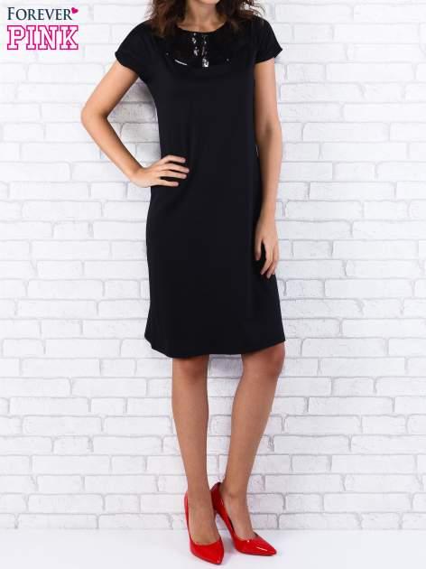 Czarna sukienka z cekinowym wykończeniem przy dekolcie