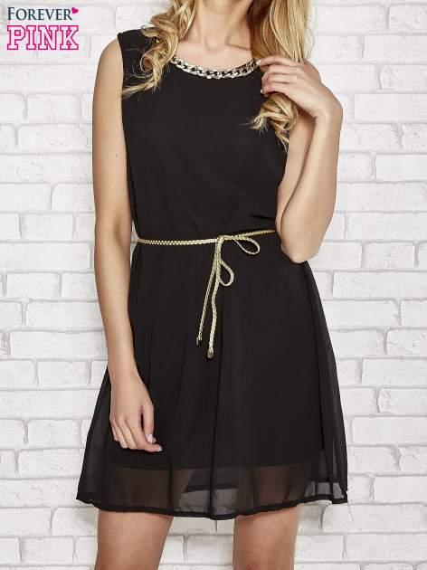 Czarna sukienka ze złotym łańcuszkiem przy dekolcie