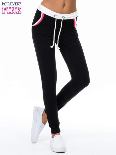 Czarne spodnie z kolorowym akcentem przy kieszeniach