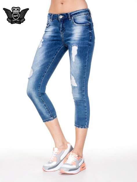 Niebieskie spodnie jeansowe do połowy łydki z przetarciami
