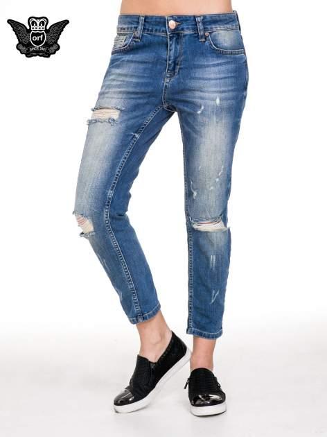 Niebieskie spodnie jeansowe rurki z dziurami i przetarciami