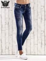 Ciemnoniebieskie jeansy rurki z przetarciami