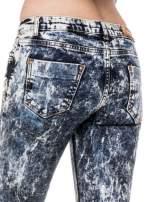 Ciemnoniebieskie mocno dekatyzowane spodnie jeansowe rurki z przetarciami