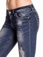 Granatowe gniecione spodnie skinny jeans z rozdarciami na kolanach