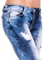 Niebieskie spodnie jeansowe rurki z rozjaśnianą i przecieraną nogawką