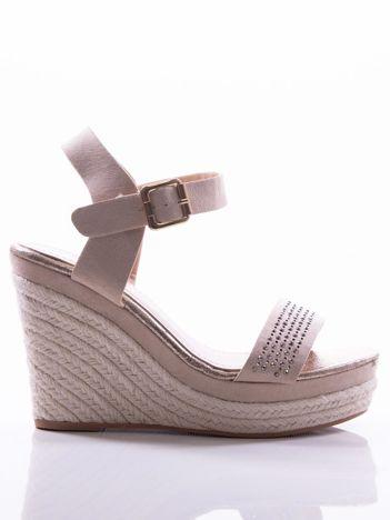 Beżowe sandały na koturnach z ażurowym paskiem na przodzie i błyszczącymi kamieniami, zapinane na pasek wokół kostki