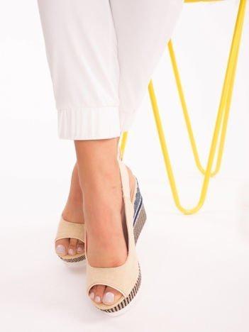 Beżowe sandały na ozdobnych koturnach z zapięciem na boku i odkrytymi piętami