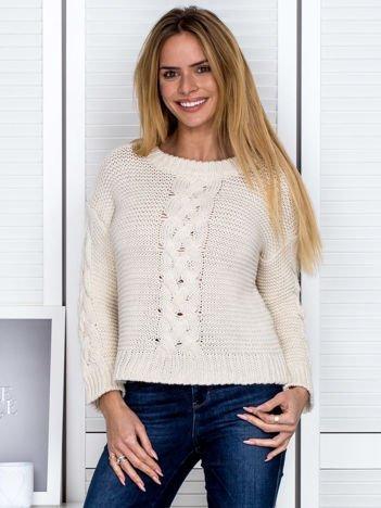 Beżowy sweter z warkoczowymi splotami