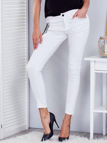 Białe spodnie z agrafkami i łańcuszkiem