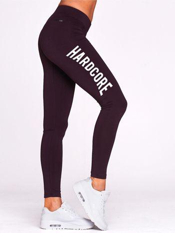 Ciemnofioletowe legginsy do fitnessu z napisem HARDCORE