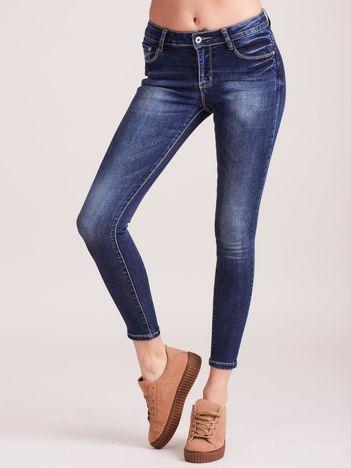 Ciemnoniebieskie przecierane jeansy