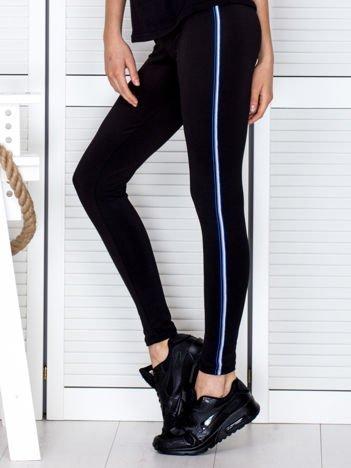 Czarne legginsy z niebieską taśmą z boku