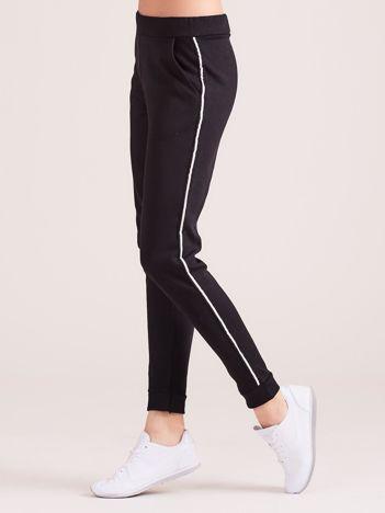 Czarne spodnie dresowe z kieszeniami i lampasem
