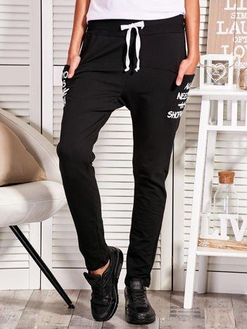 Czarne spodnie dresowe z napisami na kieszeniach