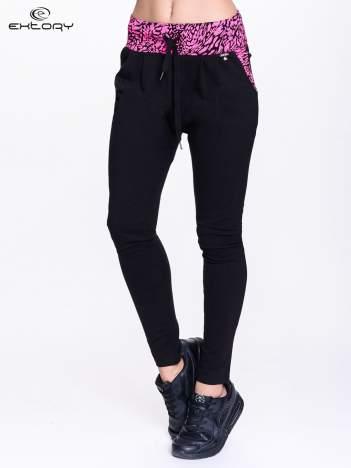 Czarne spodnie dresowe z różowym pasem w panterkę