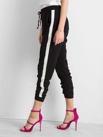 Czarne spodnie z lampasami i troczkami