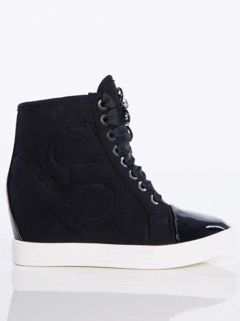 Czarne zamszowe sneakersy z tłoczoną literką na boku cholewki, sznurowane ozdobną tasiemką z błyszczącymi kamieniami na przodzie