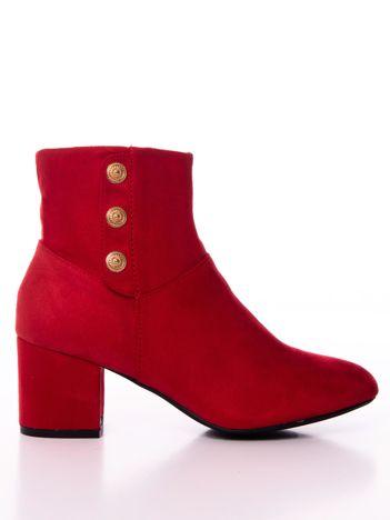 Czerwone botki ze złotymi guzikami na boku cholewki