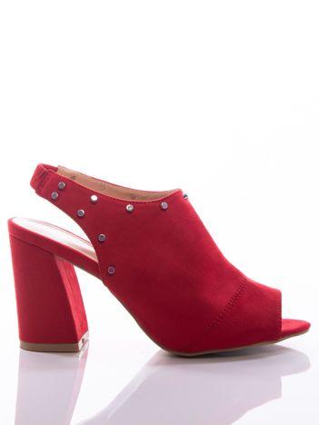 Czerwone sandały z zabudowaną cholewką, ozdobnymi ćwiekami i asymetrycznym obcasem