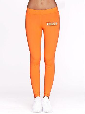 Długie fluopomarańczowe legginsy na siłownię z napisem NEVER GIVE UP