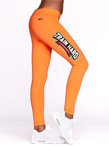 Fluo pomarańczowe legginsy treningowe z nadrukiem TRAIN HARD