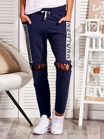 Granatowe spodnie dresowe z ażurowaniem i napisem