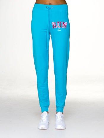 Jasnoniebieskie spodnie dresowe ze sportowym nadrukiem