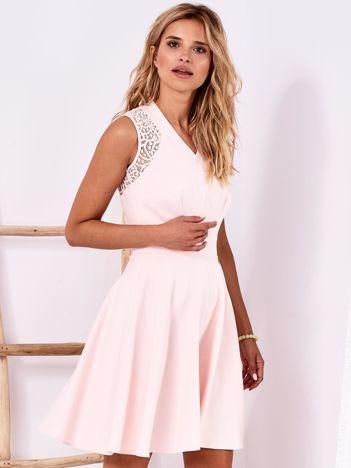 Jasnoróżowa sukienka z ażurowym wykończeniem