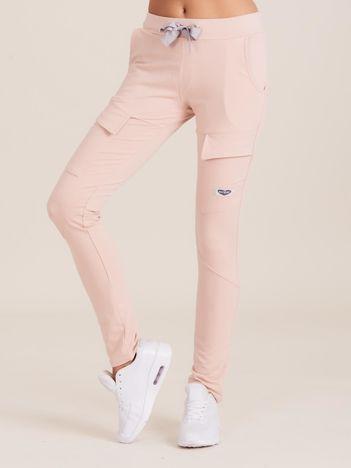 Jasnoróżowe spodnie dresowe z kieszeniami