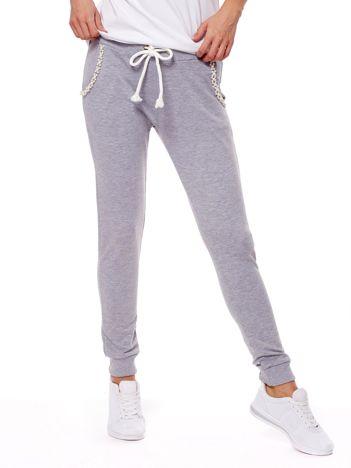 Jasnoszare spodnie dresowe z perełkami przy kieszeniach