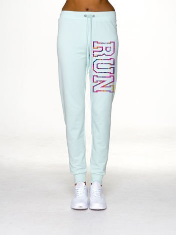 Jasnoturkusowe spodnie dresowe z napisem RUN na nogawce
