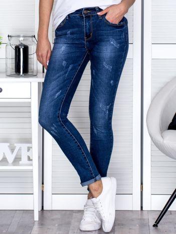 Jeansowe dopasowane spodnie z przetarciami niebieskie