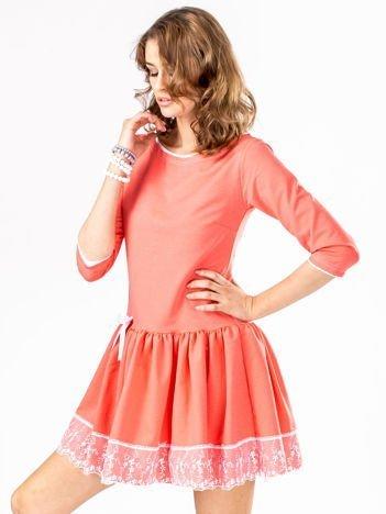 Koralowa sukienka z kokardką i szeroką falbaną