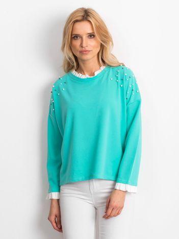 Miętowa bluzka z perełkami i kontrastowym wykończeniem