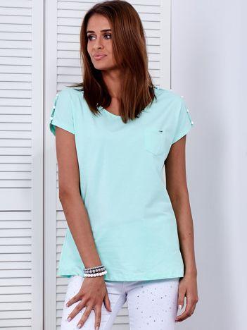 Miętowy t-shirt z kieszonką i guzikami na ramionach