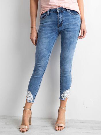 Niebieskie dopasowane jeansy z koronką