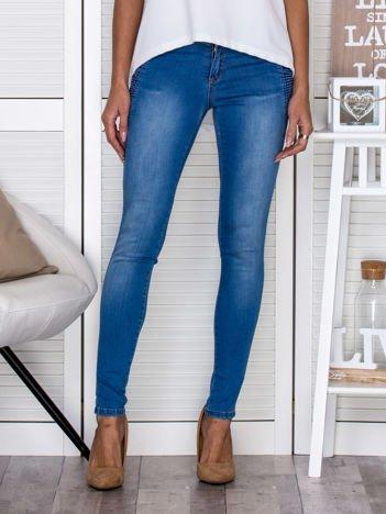 Niebieskie jeansowe spodnie rurki z marszczeniami