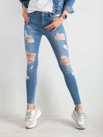 Niebieskie rurki dżinsowe z dziurami