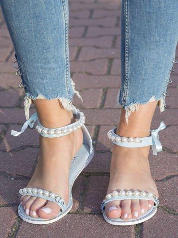 Niebieskie sandały z ozdobnymi perełkami na przodzie i wokół kostki
