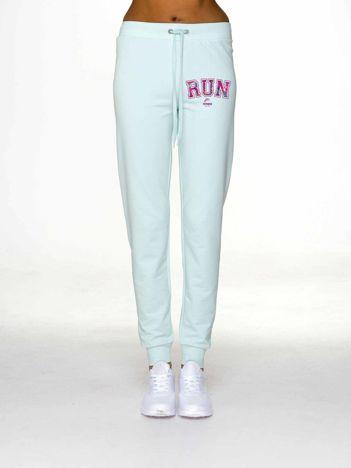Spodnie dresowe z napisem RUN jasnoturkusowe