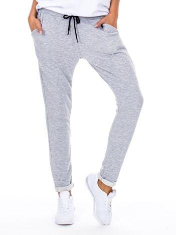 Szare spodnie dresowe z podwijanymi nogawkami