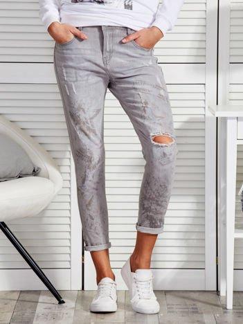 Szare spodnie z delikatnym nadrukiem i dziurami