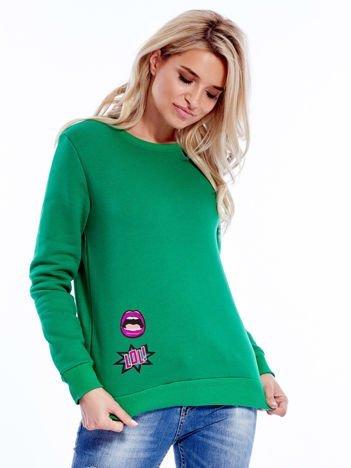 Zielona bluza damska z ozdobnymi naszywkami