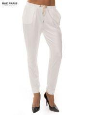 Białe spodnie dresowe ze zwężanymi nogawkami z efektem połysku