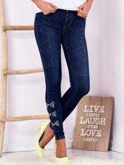 Ciemnoniebieskie jeansowe rurki z kokardkami z dżetów